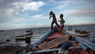"""In this Nov. 9, 2016 photo, children play """"pirates"""" on a fishing boat in Cumana, Sucre state, Venezuela. """"You hear piracy and you think of guys robbing container ships in Africa. But here it's just poor fishermen robbing other poor fishermen,"""" said Sucre lawyer Luis Morales. """"It's the same kind of crime we've seen in the streets, but spreading to the sea. (AP Photo/Rodrigo Abd)"""