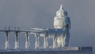 Extreme cold conditions cause ice accretions to cover the St. Joseph lighthouse and pier, on the southeastern shoreline of Lake Michigan, on Monday, Dec. 19, 2016, in St. Joseph, Mich. (Robert Franklin/South Bend Tribune via AP)