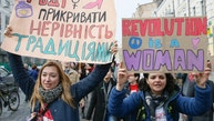 """Women hold placards during a rally for gender equality and against violence towards women on International Women's Day in Kiev, Ukraine March 8, 2017. The placard (L) reads, """"Enough to cover inequality with traditions"""". REUTERS/Valentyn Ogirenko - RTS11YBG"""
