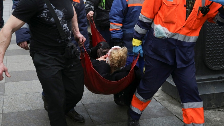 An injured person is helped by emergency services outside Sennaya Ploshchad metro station, following explosions in two train carriages at metro stations in St. Petersburg, Russia April 3, 2017. REUTERS/Anton Vaganov - RTX33UT9