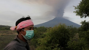 A villager walks as Mount Agung volcano erupts in the background in Kubu, Karangasem, Bali, Indonesia November 27, 2017. REUTERS/Johannes P. Christo - RC198B42A2D0