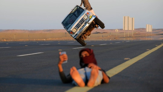 "Saudi men perform a stunt known as ""sidewall skiing"" (driving on two wheels) as a youth takes a selfie in Tabuk, Saudi Arabia March 11, 2018. REUTERS/Mohamed Al Hwaity     TPX IMAGES OF THE DAY - RC1A443944B0"