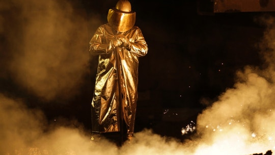 An employee in protective clothing works at the furnace  at the steel producer, the Salzgitter AG, in Salzgitter, Thursday, March 22, 2018. (AP Photo/Markus Schreiber)