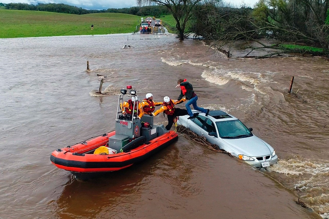 Firefighters rescue a motorist whose car became stuck as a flash flood washed over a road near Folsom, California, March 22, 2018