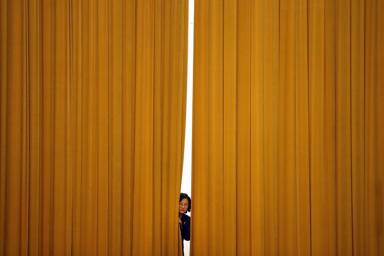 A staff member looks out from a curtain before a press conference at the Great Hall of the People in Beijing, China, March 19, 2018