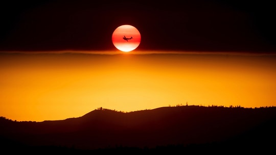 A plane battling the Ferguson Fire passes the setting sun in unincorporated Mariposa County Calif., near Yosemite National Park on Sunday, July 15, 2018. (AP Photo/Noah Berger)