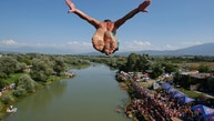 Spectators watch from the river banks as a diver launches from the Ura e Shejnt bridge during the 68th traditional annual high diving competition, near the town of Gjakova, Kosovo on Sunday, July 22, 2018 . (AP Photo/Visar Kryeziu)