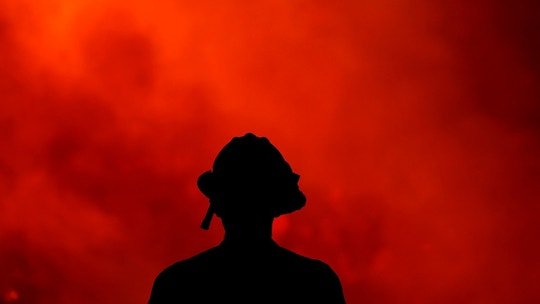 A firefighter keeps watch on the Holy Fire burning in the Cleveland National Forest in Lake Elsinore, Calif., Thursday, Aug. 9, 2018. (AP Photo/Ringo H.W. Chiu)
