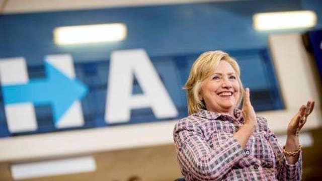 Clinton tries to woo voters by touting economic progress