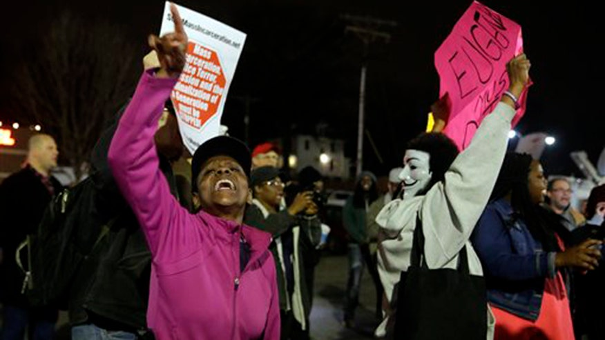Protests resume as manhunt continues for cops' shooter