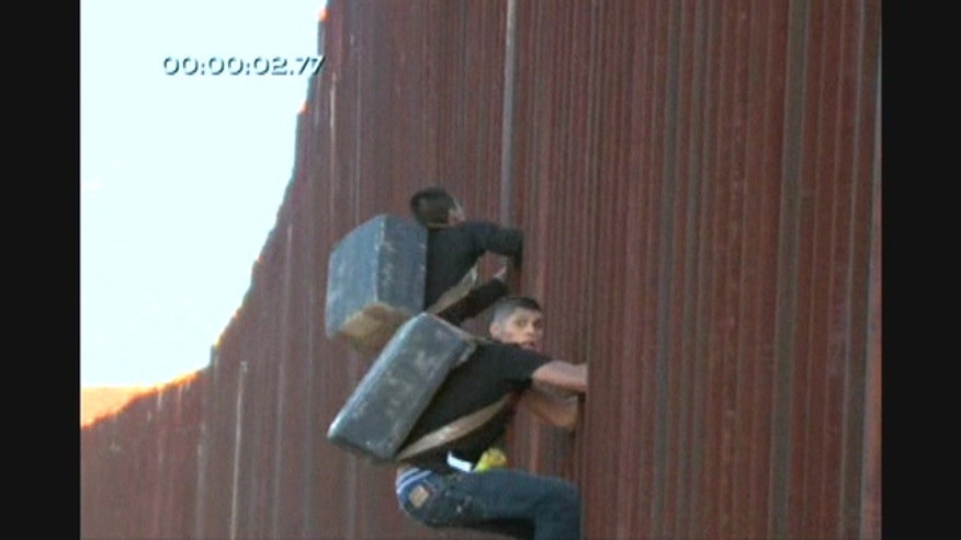 Two men were caught on video as they shimmied down the border fence which separates the United States and Mexico into Nogales, Arizona.