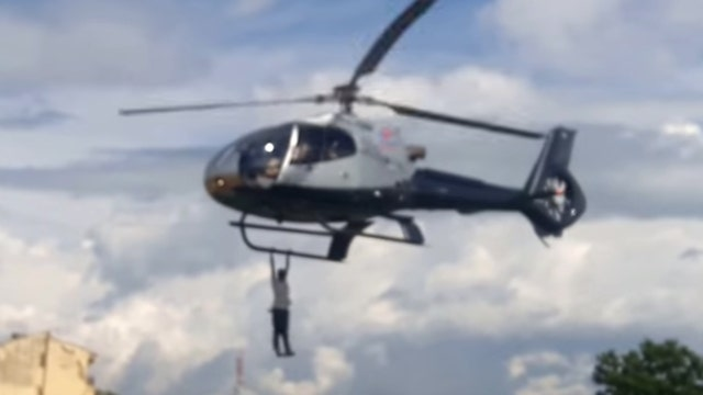 Man hangs from flying chopper for a mile