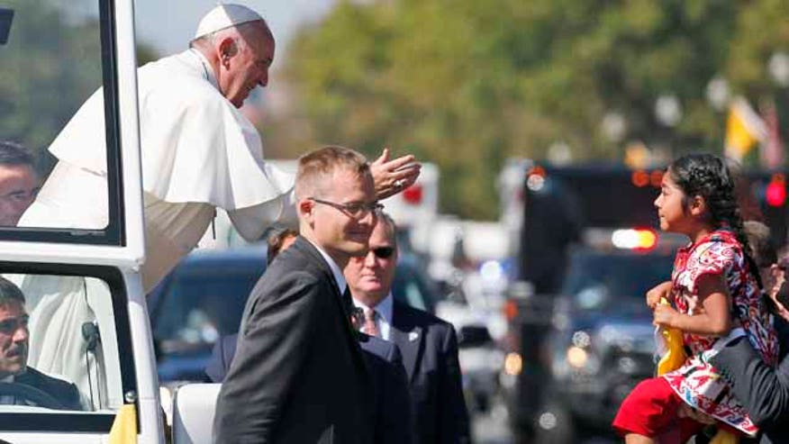 Pope Francis reaches to give a blessing to Sofia Cruz, from suburban Los Angeles, during a parade in Washington D.C.