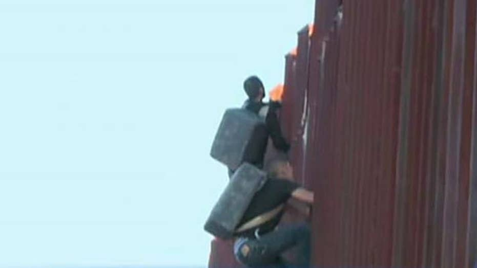 Two suspected drug smugglers caught climbing fence into US