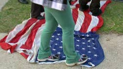 In a year when political tensions already are running high, a group of protesters is fueling the acrimony by showing up to political rallies and events with a large American flag – and stomping on it.