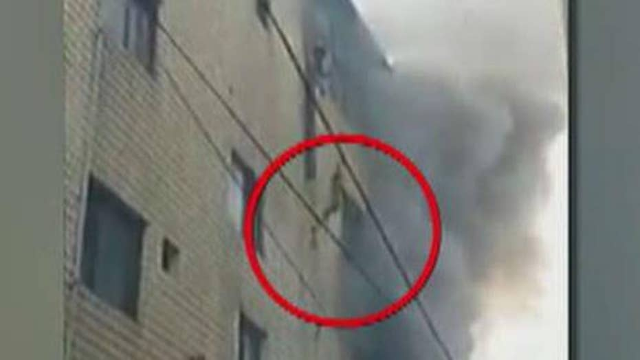 US troops help family jump to safety from burning building