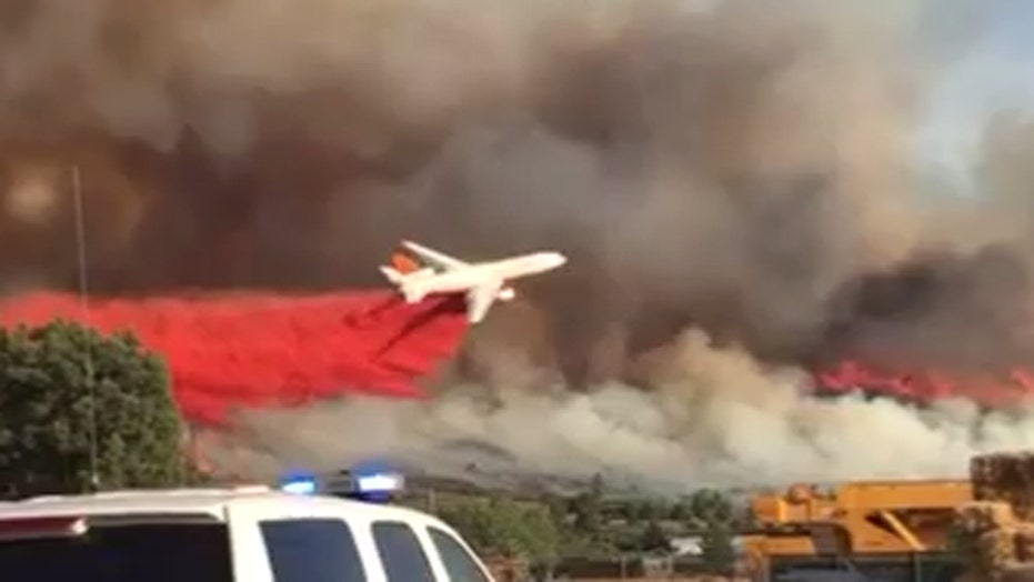 Giant tanker swoops dangerously low to douse wildfire
