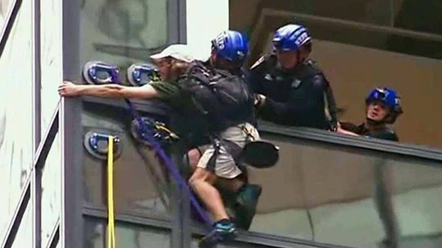 Police officers drag climber into the building through window
