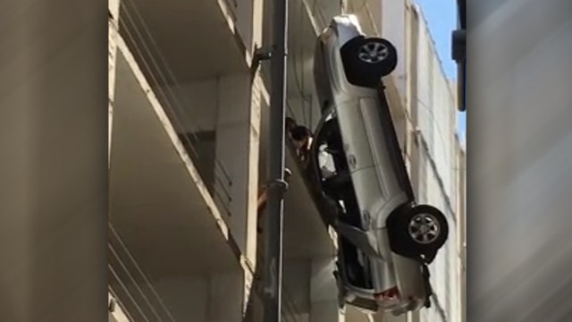 Driver escapes from dangling truck nine-stories above ground