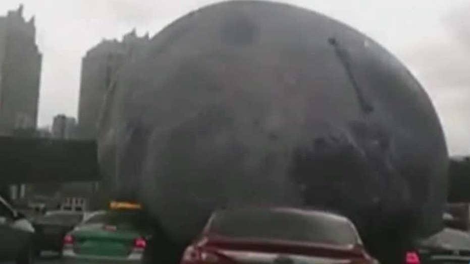 Lunacy! Deflated moon rolls through China streets