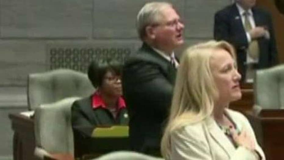 Missouri lawmaker sits during Pledge of Allegiance
