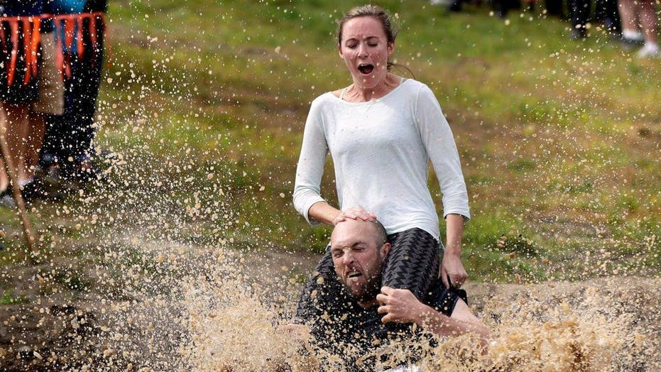 Couples compete for beer, cash in wife carrying contest