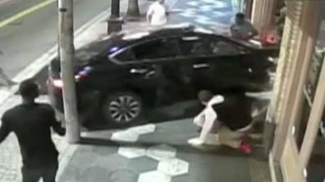 Car crashes through street brawl, into bar