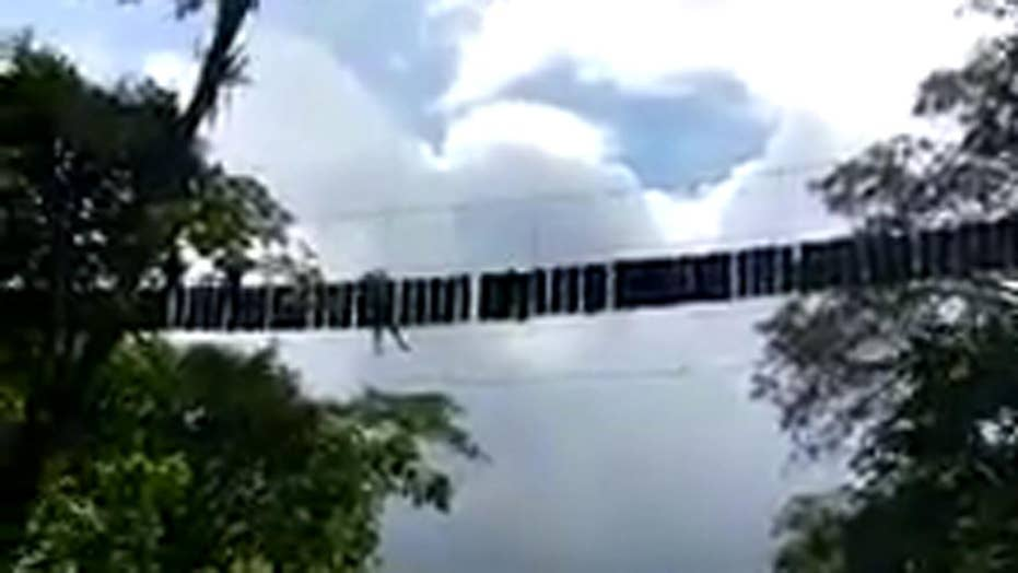 Person hangs from rope bridge after deadly collapse