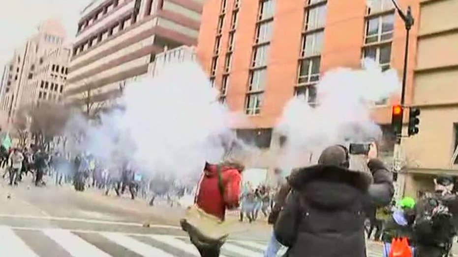 Police clashing with protesters after the inauguration
