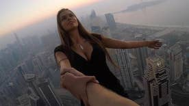 Russian Instagram model Viktoria Odintcova wows millions of followers with death-defying photo shoot, dangling off ledge of 1,000-foot building. 22-year-old faces legal action back on the ground