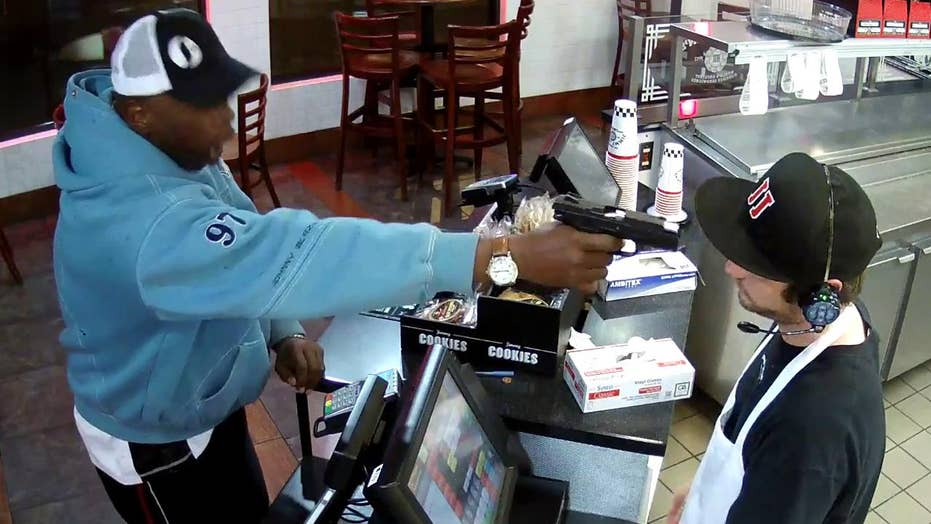 Watch clerk keep cool as thug points gun at his face