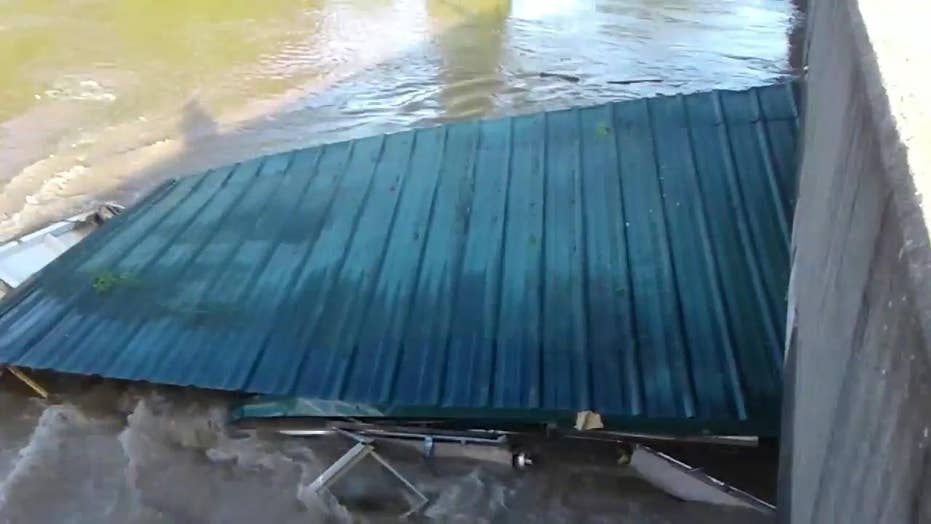 House swept up by powerful flood water, crashes into bridge