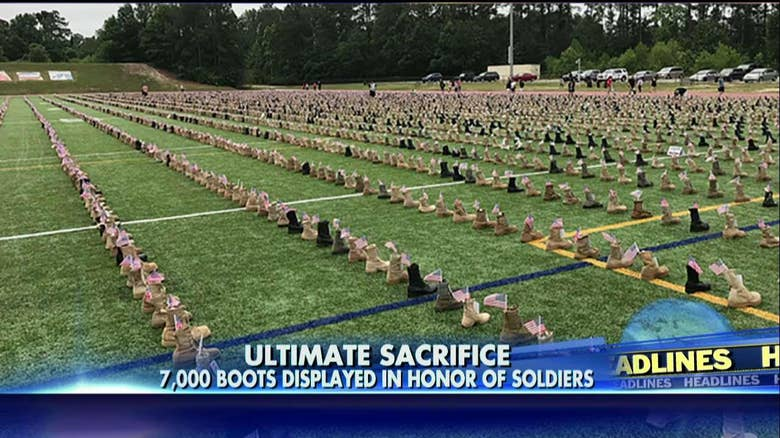 Boots lined up at Ft. Bragg, N.C. to memorialize over 7,000 US KIA since 2001 -- Photo a still of a video by Fox News Channel, reposted here for Fair Use purposes of comment or commentary