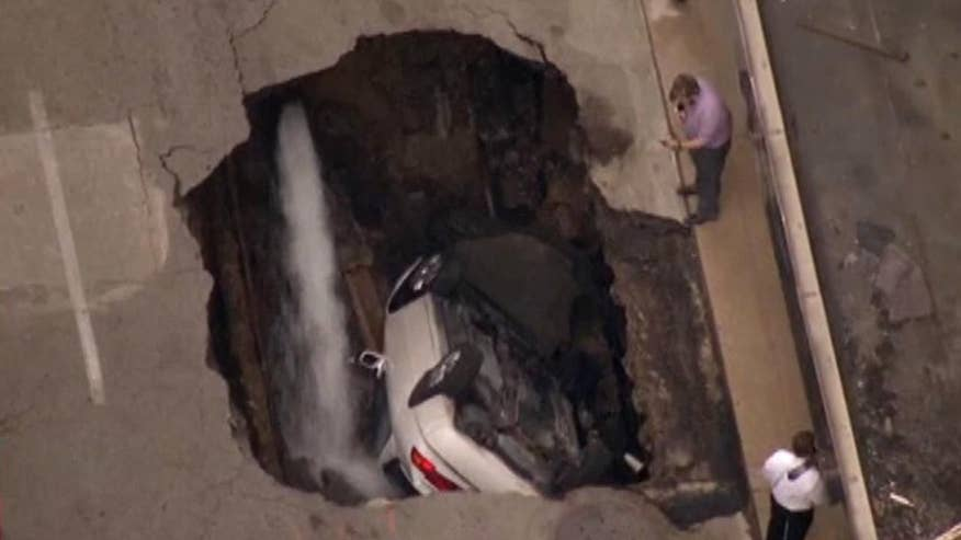 Raw video: News chopper hovers over huge hole with automobile inside