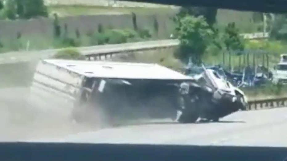 Truck flips on highway, good Samaritans rush to save driver
