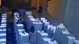 Raw video: Woman appears to crouch down to take selfie before falling backwards knocking down art in domino effect causing $200,000 worth of damage