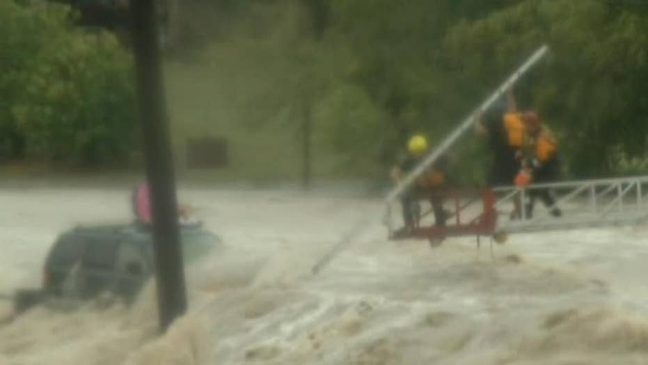 Rescue crew works to pull SUV driver from deadly floodwaters