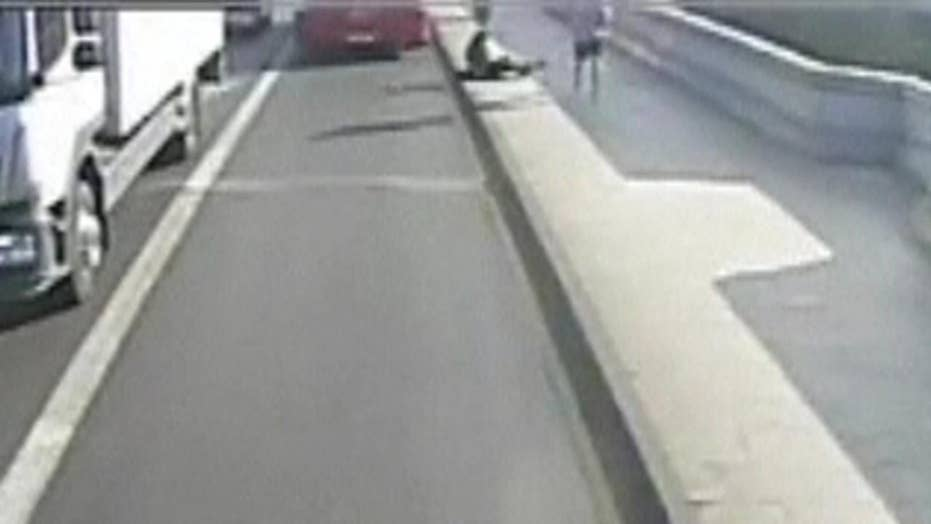 Jogger pushes woman into the road, narrowly missing a bus