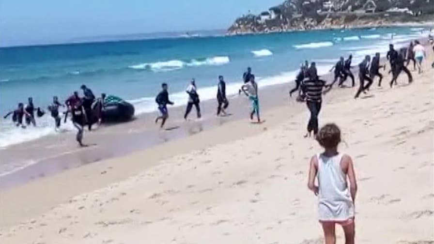 Raw video: Rubber boat packed with dozens of migrants washes up on beach in Cadiz