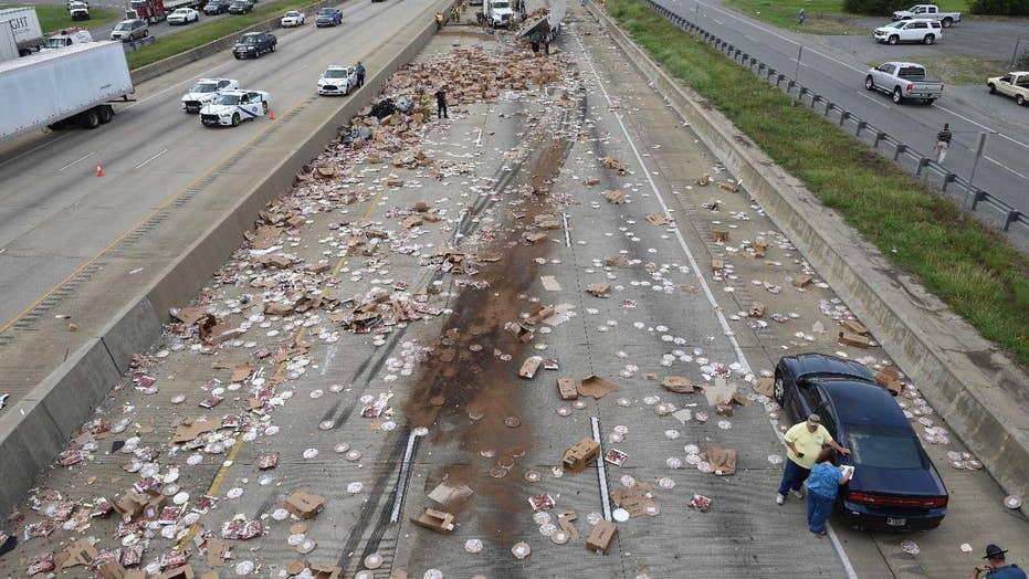 Pizza truck spills hundreds of frozen pizzas across highway