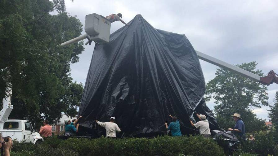 Workers in Charlottesville, Va. covered two Confederate statues in black shroud in the wake of the deadly white nationalist rally on August 12