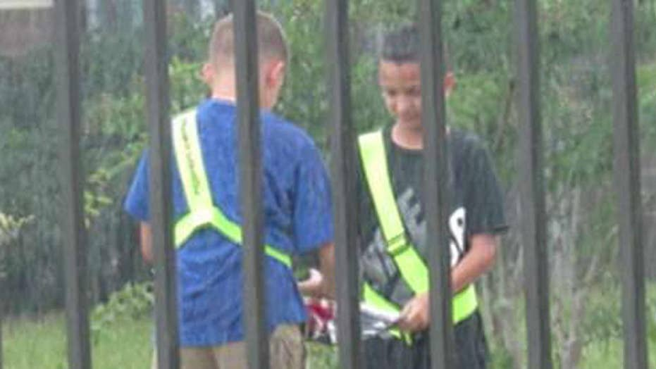 Two elementary school students fold flag in the pouring rain