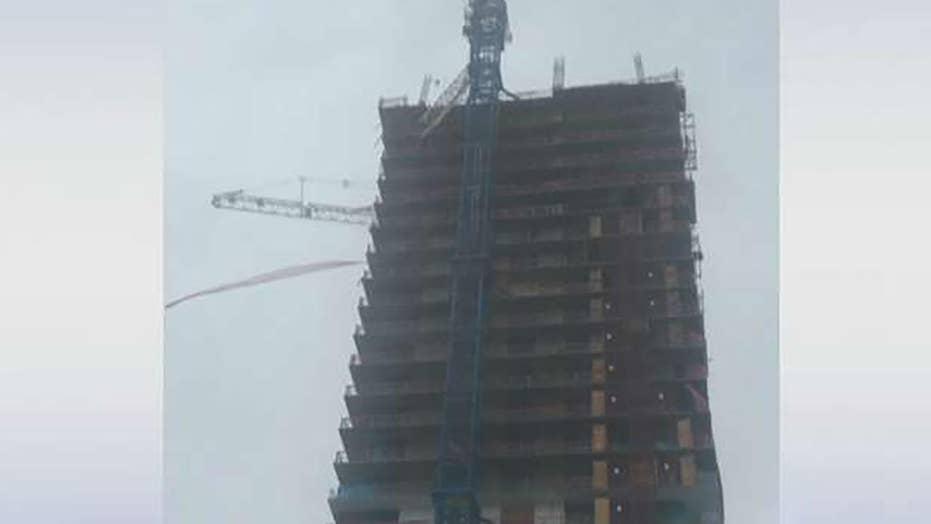 Construction crane collapses onto building in Miami