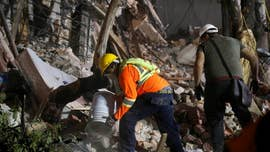"Desperate searchers shouted ""quiet"" and listened for faint voices in the rubble where a Mexican school once stood, as rescuers used trained dogs and their bare hands to reach any survivors of Tuesday's magnitude-7.1 earthquake that killed more than 200 people."