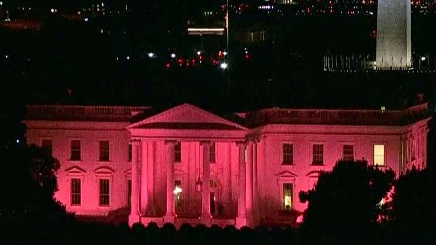 colored lights shine on White House facade.
