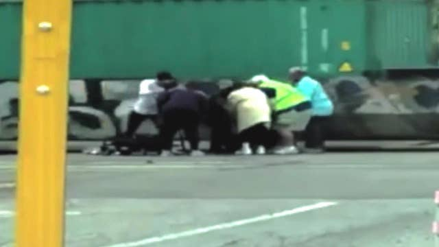 Woman saves man in wheelchair stuck on train tracks