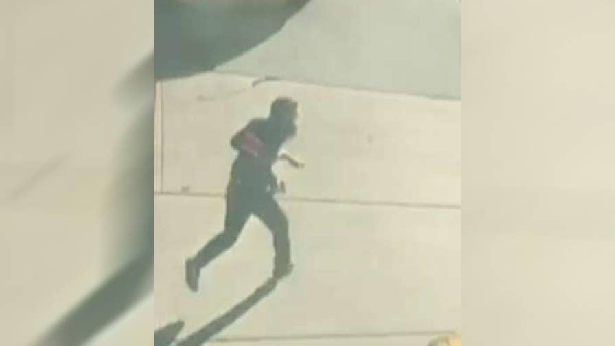 Eyewitness records video of suspect running through traffic, brandishing what appear to be handguns.