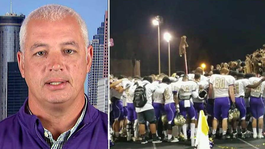 High schoolers rally behind Coach John Small after the district barred him from participating in student-led prayer after he was reported by an atheist group.
