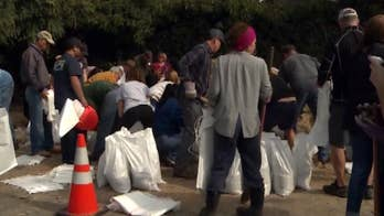 People fill sandbags to prep homes for rain storm that could bring flooding, debris flows to burn areas.