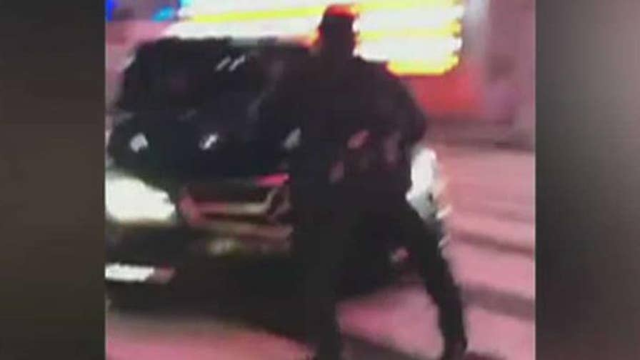 Black Mercedes sedan speeds away from scene in New York City.